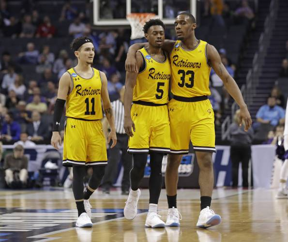 5f823d37bc8 UMBC's Arkel Lamar, Jourdan Grant and K.J. Maura, from right, embrace as  they leave the court in the closing moments of the team's 50-43 loss to  Kansas ...
