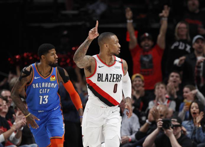 db9decc9898 Portland Trail Blazers guard Damian Lillard, right, reacts after making a  basket as Oklahoma City Thunder forward Paul George, left, trails the play  during ...