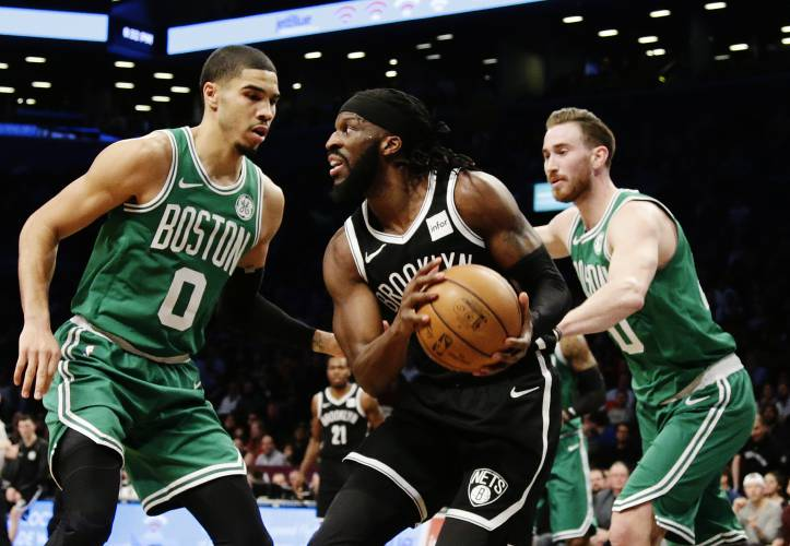 brooklyn nets demarre carroll 9 is defended by boston celtics jayson tatum 0 and gordon hayward during the first half of an nba basketball game monday
