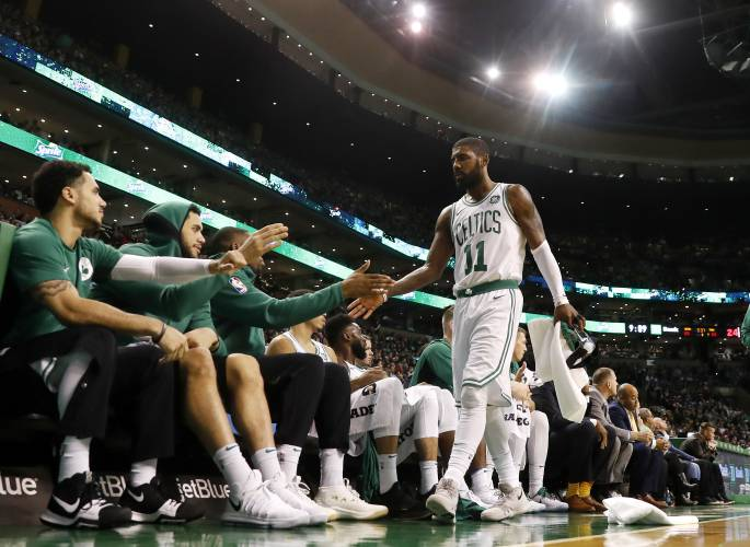 52e770529ee1 Boston Celtics  Kyrie Irving is congratulated at the bench by teammates  during the third quarter of an NBA basketball game against the Philadelphia  76ers in ...