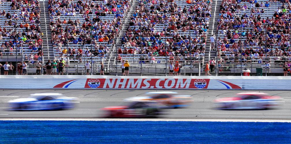 Cars Steer Through Turn 1 As Fans Watch From Nearly Half Full Stands During The Nascar Cup Series 301 Auto Race At New Hampshire Motor Speedway In Loudon