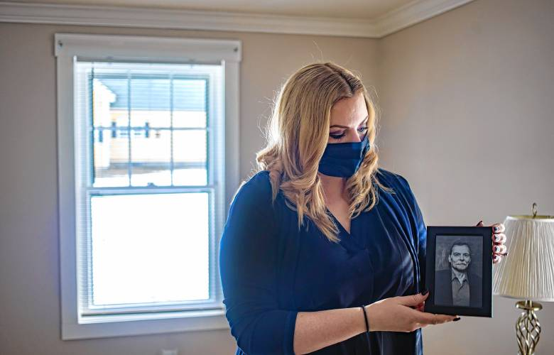 Kara Pioli holds a photo of her father, William Pioli, in the guest room of her Penacook home on Friday. Her father died of COVID last year.