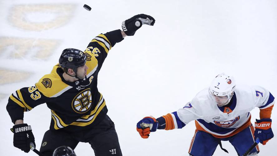 f7bd637f8d6 Boston Bruins defenseman Zdeno Chara (33) and New York Islanders right wing  Jordan Eberle (7) try to knock down a flying puck during first period of an  NHL ...